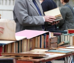 Man looking at books which can be catalogued onto an online catalogue using library software