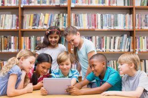 Children sitting in a school library with an ipad looking at the online catalogue of their Simple Little Library System