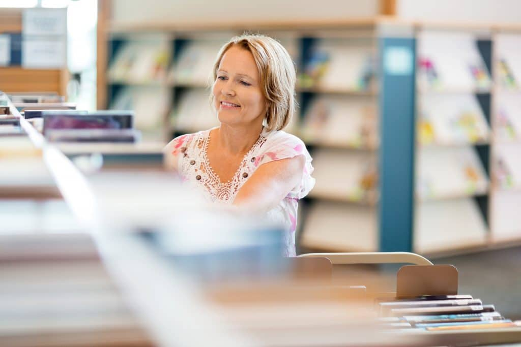 Librarian working in library surrounded by books