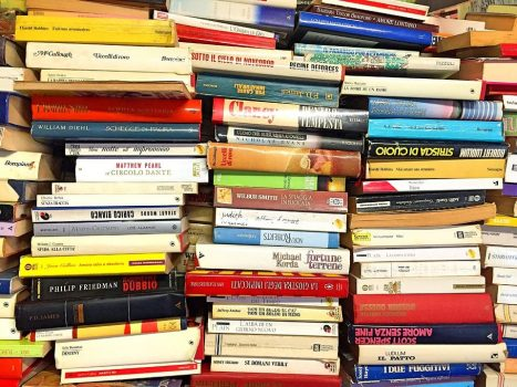 Stack of books that need cataloguing into a library system